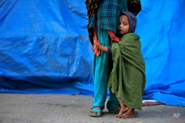 A Bangladeshi child holds his mother, who awaits work with other daily wage laborers during the second day of 72 hours long strike called by the opposition Bangladesh Nationalist Party (BNP) led alliance in Dhaka, Bangladesh, Monday, Feb. 2, 2015. Since Jan.5, the BNP has been blockading Dhaka demanding that the government resign and hold new elections immediately, but Prime Minister Sheikh Hasina says her government will remain in office until her term ends in 2019. (AP Photo/ A.M. Ahad)