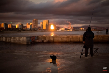 A cat sits near to a man fishing on a breakwater facing the Mediterranean sea, in Barcelona, Spain, on Tuesday, Feb. 3, 2015. (AP Photo/Emilio Morenatti)