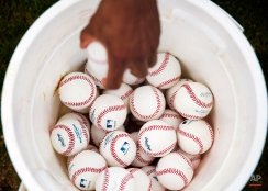 Baseballs sit in a bucket as Houston Astros pitcher Tony Sipp reaches in to grab one during a spring training baseball workout, Tuesday, Feb. 24, 2015, in Kissimmee, Fla. (AP Photo/David Goldman)