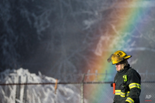 A firefighter walks past refracted light and a building covered in ice from their water canons as the fire crew battled a blaze, Tuesday, Feb. 24, 2015, in the Kensington neighborhood of Philadelphia. The fire started in a building housing retail shops and no injuries were reported. (AP Photo/Matt Rourke)