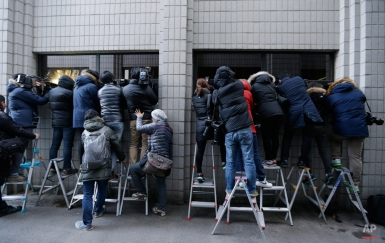 Members of the media try to get pictures of a bus carrying Cho Hyun-ah, the former vice president of Korean Air Line Co., through the windows of the Seoul Western District Court after her trial in Seoul, South Korea, Thursday, Feb. 12, 2015. A Seoul court on Thursday sentenced Cho to a year in prison for aviation law violations that stemmed from her inflight tantrum over how she was served macadamia nuts. (AP Photo/Ahn Young-joon)