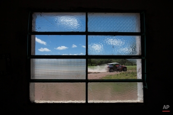 The broken window of a home frames Mini driver Boris Garafulic, from Chile, and co-pilot Filipe Palmeiro, from Portugal, as they race in the eleventh stage of the Dakar Rally between the cities of Termas de Rio Hondo and Rosario, Argentina, Friday, Jan. 16, 2015. (AP Photo/Felipe Dana)