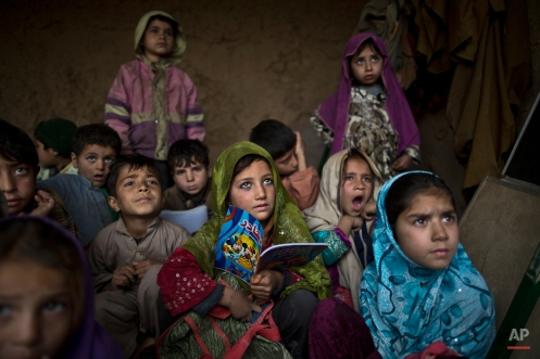 Afghan refugees and internally displaced Pakistani children gather in a mud house to learn from a man volunteering to teach them how to write the alphabet at a makeshift school in the outskirts of Islamabad, Pakistan, Tuesday, Feb. 3, 2015. (AP Photo/Muhammed Muheisen)