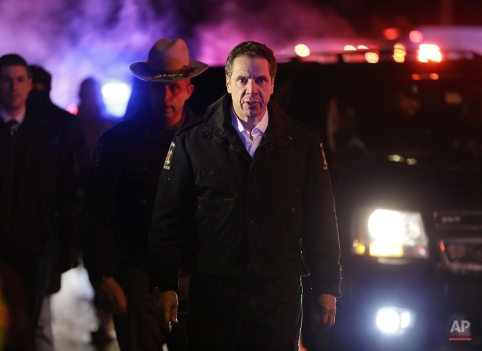 New York Gov. Andrew Cuomo arrives to the site of a collision between a train and vehicle in Valhalla, N.Y., Tuesday, Feb. 3, 2015. A packed commuter train slammed into a sport utility vehicle on the tracks and the front of the train and the vehicle burst into flames, authorities said. (AP Photo/Seth Wenig)