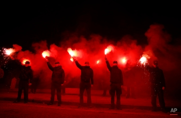 """Supporters of Greece's extreme right party Golden Dawn hold flares during a rally to commemorate a 1996 incident which cost the lives of three Greek navy officers and brought Greece and Turkey to the brink of war, in Athens on Saturday, Jan. 31, 2015. The extreme right, anti-immigrant Golden Dawn party, which has Nazi roots, appears headed for a third-place finish in last Sunday's election. Its showing comes despite the fact that the party's leader and most of its lawmakers are behind bars, facing charges of participating in a """"criminal organization"""" accused of murders, brutal attacks on migrants and others, extortion and arson. (AP Photo/Lefteris Pitarakis)"""