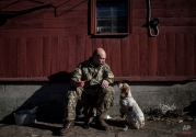 Vasily Yakovenko, captain of a Ukrainian military medical unit, pats a dog near the village of Luhanske, eastern Ukraine, Tuesday, Feb. 24, 2015. Ukrainian officials said they haven't yet started pulling heavy weapons back from a frontline in eastern Ukraine because of continued rebel violations of a cease-fire deal. (AP Photo/Evgeniy Maloletka)
