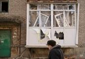 A woman walks outside a heavily damaged apartment building in Debaltseve, Ukraine, Monday, Feb. 23, 2015. After weeks of relentless fighting, the embattled Ukrainian rail hub of Debaltseve fell last week to Russia-backed separatists. (AP Photo/Vadim Ghirda)