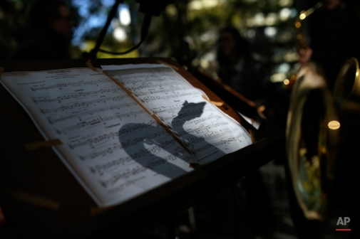 The shadow of a saxophone is cast on some sheet music as musicians perform during a protest by Portuguese state school music teachers outside the Portuguese Education Ministry, in Lisbon, Monday, Feb. 9, 2015. Music teachers and students performed on a small stage outside the Ministry protesting against budget arrears for music and dance schools since September 2014. (AP Photo/Francisco Seco)