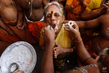 A Hindu woman devotee gets her cheeks pierced with a metal rod as she participates in a religious procession during Thaipusam festival in Chennai, India, Tuesday, Feb. 3, 2015. Thaipusam, which is celebrated in honor of Hindu god Lord Murugan, is an annual procession by Hindu devotees seeking blessings, fulfilling vows and offering thanks. (AP Photo/Arun Sankar K)