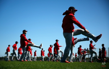 Members of the St. Louis Cardinals stretch at the start of the first official spring training baseball practice for pitchers and catchers, Friday, Feb. 20, 2015, in Jupiter, Fla. (AP Photo/Jeff Roberson)