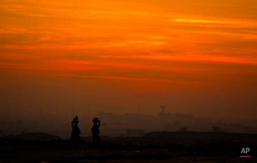 Pakistani nomad women carry water to their houses at dusk in Islamabad, Pakistan, Thursday, Feb 12, 2015. People living in suburbs of the capital are lacking basic necessities of life. (AP Photo/B.K. Bangash)