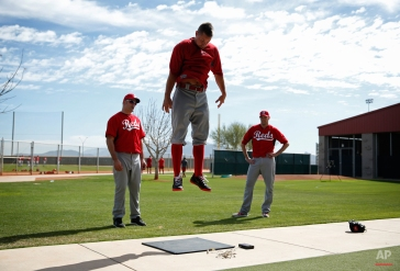 Cincinnati Reds' Mike Leake measures how high he can jump during the baseball team's first practice for pitchers and catchers at spring training this season, Thursday, Feb. 19, 2015, in Goodyear, Ariz. (AP Photo/John Locher)