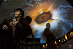 Visitors examine the 'My History. Rurikovichi' multimedia exhibition devoted to the period of Rurikovichi (Rurik dynasty) in St. Petersburg, Russia, Thursday, Feb. 12, 2015, with the Orthodox icon of Jesus projected on the ceiling. The exhibition displays Russia's history spanning seven centuries. (AP Photo/Dmitry Lovetsky)