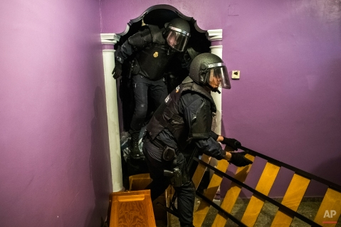 Police enter the apartment of Emilia Montoya Vazquez by forcing their way in between furniture after they broke down the main door to evict her and her family in Madrid, Spain, Wednesday, Feb. 25, 2015. Montoya, who lived with her son and daughter in law, both unemployed, and three grandchildren of 7, 6, 3 years old, had accumulated a debt with the (EMV) City Hall Housing Company as she could not afford to pay rent due to her only income being a state benefit of 460 euros ($522) a month. The eviction was carried out in spite dozens of housing right activists who gathered inside the apartment and blocked the main door. EMVS, a state company with an aim to give housing solutions for people in need, sold 1.860 state apartments to private investors, last year. (AP Photo/Andres Kudacki)