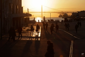 People walk to take a ferry at the Terreiro do Paco terminal port, in Lisbon, Monday, Feb. 9, 2015. Every working day during the week thousands of commuters cross and back the Tagus river by ferry to reach their jobs in the Portuguese capital. (AP Photo/Francisco Seco)