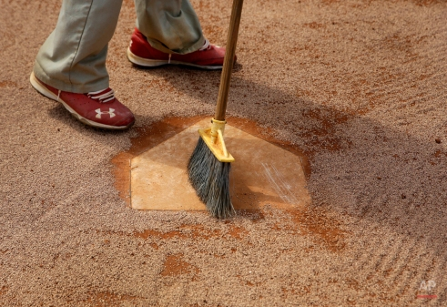 Rodger Dean Stadium grounds crew member Antoine Stubbs sweeps off home plate in a bullpen at the St. Louis Cardinals spring training baseball practice facility, Wednesday, Feb. 18, 2015, in Jupiter, Fla. (AP Photo/Jeff Roberson)