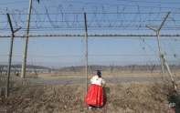 South Korean Park Yeon-hee wearing a traditional costume looks over to North Korean side through a barbed wire fence as her family members visit to respect for their ancestors in North Korea on the Lunar New Year at the Imjingak Pavilion, near the demilitarized zone of Panmunjom, in Paju, South Korea, Thursday, Feb. 19, 2015. Millions of South Koreans will visit their hometowns during the three-day holiday that began Wednesday. (AP Photo/Ahn Young-joon)