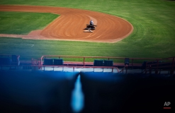 A member of the grounds crew grooms the infield of Space Coast Stadium, the spring training home of the Washington Nationals baseball team, Wednesday, Feb. 18, 2015, in Viera, Fla. Washington Nationals pitchers and catchers officially report for spring training baseball Thursday, Feb. 19, 2015. (AP Photo/David Goldman)