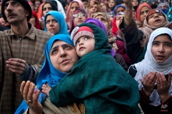 A Kashmiri Muslim woman carries her daughter while praying as the head priest displays a relic of Sufi saint Syed Abdul Qadir Jilani at his shrine in Srinagar, India, Friday, Feb. 6, 2015. Thousands of devotees thronged to the shrine which houses the relic of the saint on the Friday following the saint's Urs, or yearly commemoration. (AP Photo/Dar Yasin)