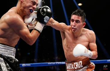 Leo Santa Cruz hits Jesus Ruiz during their WBC super bantamweight title bout Saturday, Jan. 17, 2015, in Las Vegas. (AP Photo/John Locher)