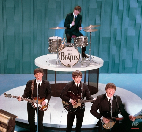 """The Beatles perform on the the """"Ed Sullivan Show"""" in New York on February 9, 1964. From left, front, are Paul McCartney, George Harrison and John Lennon. Ringo Starr plays drums. (AP Photo)"""