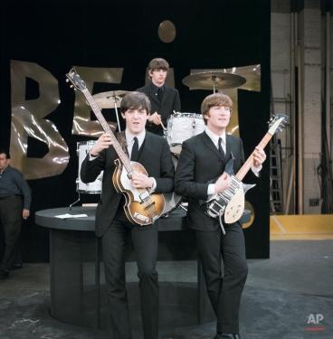 "Three members of the Beatles, from left, Paul McCartney, left, John Lennon and drummer Ringo Starr are shown on the set of ""The Ed Sullivan Show"" in New York, Feb. 8, 1964. (AP Photo)"
