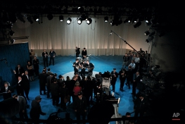 The British rock and roll group the Beatles, center, are surrounded by photographers on stage at CBS' Studio 50 before their live television appearance on The Ed Sullivan Show in New York City, Feb. 10, 1964. In the front row are, from left, Paul McCartney, George Harrison and John Lennon. Ringo Starr is in background on drums. (AP Photo)