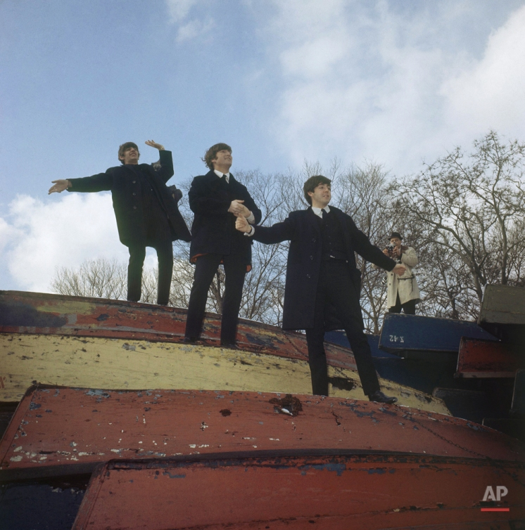 In this Feb. 10, 1964, photo, three members of the Beatles pose on a stack of rowboats in New York's Central Park. From the top are: Ringo Starr, John Lennon and Paul McCartney. (AP Photo)