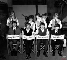 """The Beatles, George Harrison, Ringo Starr, Paul McCartney and John Lennon, have their hair combed by stylists on the set of their first movie production, """"A Hard Day's Night,"""" at Twickenham Film Studios in Middlesex, outside London, England, on March 12, 1964. The hair stylists, who have parts in the film, are, from left, Patti Boyd, 19, Tina Williams, 17, Pru Bury, 22, and Susan Whitman, 17. (AP Photo)"""