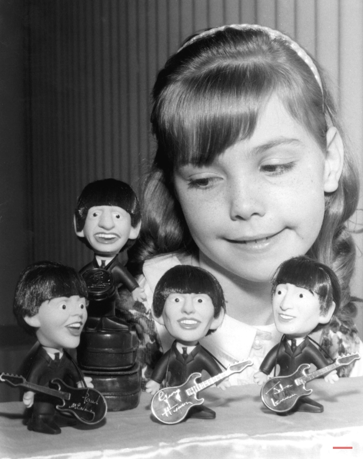 Aren't they Dolls? The impact of the Beatles is reflected at the current toy Fair in New York. Beatle dolls are among the toys in the new group which will be in stores for the fall and Christmas season, or earlier. The Beatles dolls, which are caricatures of the English characters, are looked over by Carol Valentine, March 10, 1964. (AP Photo)