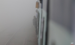 Passengers stand by the door of a moving train surrounded by fog in Rewari, in the northern Indian state of Haryana, Wednesday, Feb. 18, 2015. Even though minimum temperature was reported to have increased, thick fog was seen Wednesday morning in the region. (AP Photo/Ajit Solanki)