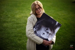 Jennifer Conforti, of Fayetteville, Ga., holds a portrait of her autistic daughter, Abby, 4, while attending a rally in favor of House Bill 1, which would legalize possession of cannabis oil for treatment of certain illnesses, Tuesday, Feb. 3, 2015, in Atlanta. Abby suffers from seizures and Conforti believes the cannabis oil would help her daughter. The bill goes before a committee for testimony hearings Tuesday. (AP Photo/David Goldman)