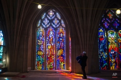 A reporter, standing on a scaffold platform 65 feet above the nave floor, takes a photograph of a recently cleaned and repaired stained glass window at the Washington National Cathedral in Washington, Wednesday, Feb. 18, 2015. This marks the completion of the first phase in the building's $32 million restoration effort. (AP Photo/Cliff Owen)
