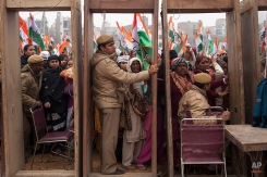 India's opposition Congress party supporters wait to enter the rally ground as policemen wait beside security gates during an election campaign rally ahead of Delhi state election in New Delhi, India, Wednesday, Feb. 4, 2015. Delhi goes to the polls on Feb. 7. (AP Photo/Tsering Topgyal)