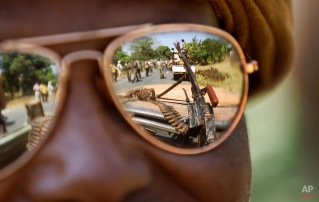 A Chadian soldier wearing reflective sunglasses observes the convoy ahead of him, as Chadian soldiers who are fighting in support of Central African Republic president Francois Bozize, ride on the road leading to Damara, about 70km (44 miles) north of the capital Bangui, Central African Republic Wednesday, Jan. 2, 2013. (AP Photo/Ben Curtis)