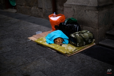 A dog lies down as its owner begs on a street nearby in Madrid, Spain, Wednesday, Feb. 11, 2015. (AP Photo/Emilio Morenatti)