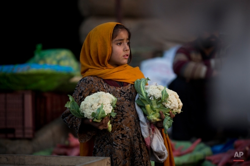 A Pakistani girl, who is displaced with her family from a Pakistani tribal area due to security forces' operations against militants, waits for customers to buy cauliflower at a fruit and vegetable market in Islamabad, Pakistan, Monday, Feb. 9, 2015. (AP Photo/B.K. Bangash)