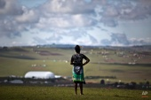 A mourner wearing a banner as a skirt showing the face of South African President Jacob Zuma observes the scene from a hilltop overlooking the burial site of Nelson Mandela in Qunu, South Africa Sunday, Dec. 15, 2013. (AP Photo/Ben Curtis)