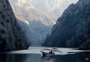 Two people in a small boat sail along Treska River at Matka Canyon, west of Skopje, in Macedonia, Sunday, Feb. 15, 2015. Rivers and water accumulations are full after a period of heavy rains in this Balkan country. (AP Photo/Boris Grdanoski)