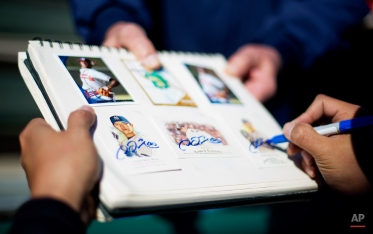 Atlanta Braves pitcher Chien-Ming Wang, of Taiwan, signs his baseball cards for a fan following an informal spring training baseball workout, Friday, Feb. 20, 2015, in Kissimmee, Fla. (AP Photo/David Goldman)
