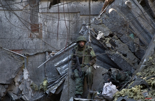 A Russia-backed rebel leans against a wall of the destroyed building of the airport while guarding Ukrainian POWs, outside Donetsk, Ukraine, Wednesday, Feb. 25, 2015. Ukrainian troops held captive in the separatist stronghold of Donetsk began digging through the rubble Wednesday to retrieve the bodies of fellow soldiers killed last month in a bitter battle for the city's airport. (AP Photo/Vadim Ghirda)