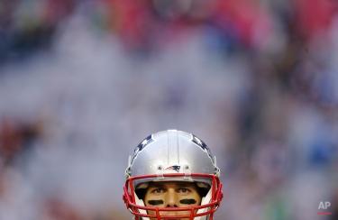 New England Patriots quarterback Tom Brady (12) watches during warm ups before the NFL Super Bowl XLIX football game against the Seattle Seahawks, Sunday, Feb. 1, 2015, in Glendale, Ariz. (AP Photo/Patrick Semansky)