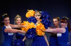 Dancers in cheerleader costumes pose for the photographers next to a wax figure of U.S. singer Taylor Swift during a photo call in central London, Tuesday, Feb. 10, 2015. The new wax figure was unveiled at the Madame Tussauds London attraction. (AP Photo/Lefteris Pitarakis)