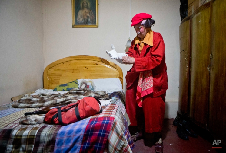 """In this Feb. 7, 2015 photo, veteran clown Ricardo Farfan, popularly known as """"Pitito,"""" puts on his costume as he prepares to perform at his 91st birthday party inside his home in Lima, Peru. (AP Photo/Esteban Felix)"""