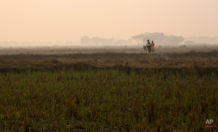 A man rides a bicycle with a woman on a road through rice fields at dawn in Dala, a suburb of Yangon, Myanmar Tuesday, Feb. 3, 2015. (AP Photo/Gemunu Amarasinghe)