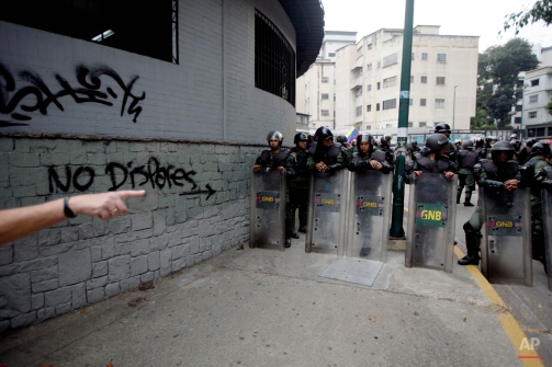 """Bolivarian National Guard officers dressed in riot gear, lineup next to graffiti that reads in Spanish """"Don't shoot"""" during the anniversary of the protest movement that wracked the country last year in Caracas, Venezuela, Thursday, Feb. 12, 2015. Friends and foes of Venezuela's socialist government braved pouring rain to stage dueling marches in the capital. (AP Photo/Fernando Llano)"""