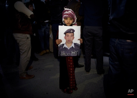 """A Jordanian child holds a poster with a picture of Jordanian pilot, Lt. Muath al-Kaseasbeh, who is held by the Islamic State group militants, with Arabic that reads, """"we are all Muath,"""" during a candle vigil in support of Japan, in front of the Japanese embassy, in Amman, Jordan, Monday, Feb. 2, 2015. The wife of slain Japanese hostage Kenji Goto said Monday that she was devastated but proud of her husband, who was beheaded by Islamic State extremists. (AP Photo/Nasser Nasser)"""