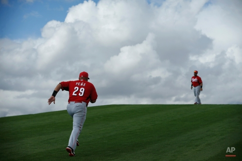 Cincinnati Reds' Brayan Pena, left, runs up a hill during a spring training baseball workout, Monday, Feb. 23, 2015, in Goodyear, Ariz. (AP Photo/John Locher)