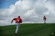 Cincinnati Reds' Brayan Pena, left, runs up a hill during a spring training baseball workout Monday, Feb. 23, 2015, in Goodyear, Ariz. (AP Photo/John Locher)
