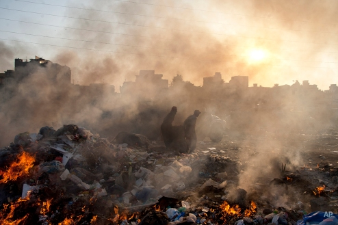 Afghan refugees collect recyclable items from a heap of garbage to earn their living, Wednesday, Jan. 28, 2015. (AP Photo/Shakil Adil)